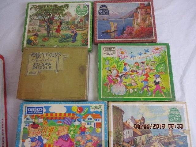 A collection of Victory wooden jigsaws Pigs at market 43pcs , Children in garden 100pcs , Yatch scene 75 pcs , Seaside scene 100 pcs , Pixies supermarket 20 pcs and Thatch cottage scene 400 pcs .  image