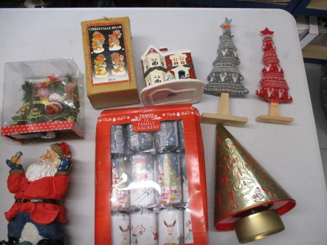 Christmas assortment to include crackers, christmas bear, santa, ornamental trees etc.  image